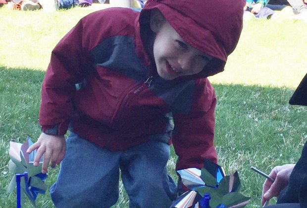 "Child ""plants"" a pinwheel in Hamilton Township earlier this month as part of a demonstration for child abuse prevention. (Courtesy of Hamilton Area YMCA)"